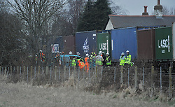 © Licensed to London News Pictures. 2/1/2013. Emergency services stood next to the wreckage of a car at the scene where a man died when his car is hit by a freight train on a level crossing on Sandy Lane between Yarnton and Kidlington in Oxfordshire. The man was declared dead at the scene. Photo credit: MarkHemsworth/LNP