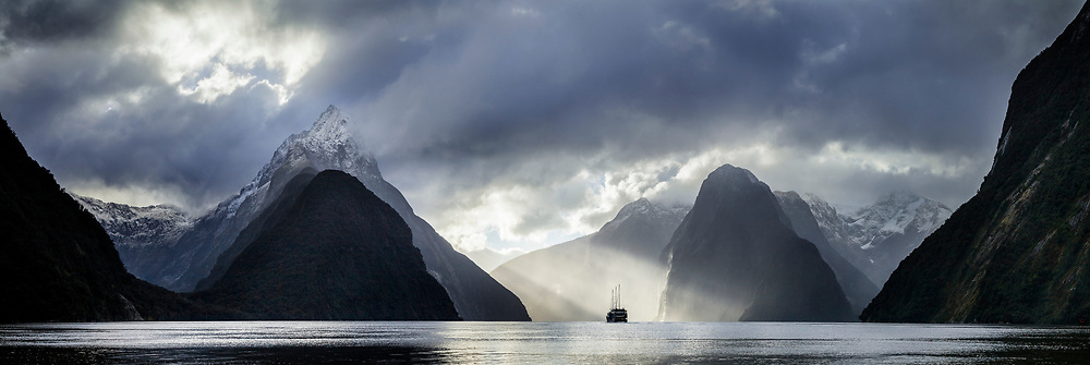 A three masted tourist boat heads out past Mitre Peak in Milford Sound.