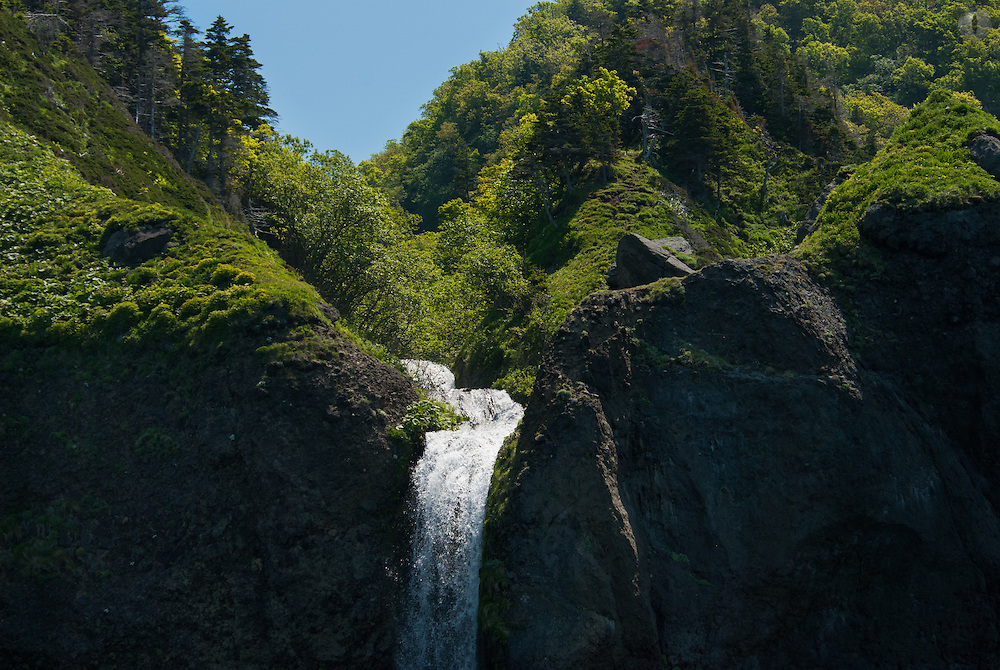 The Shiretoko peninsula in Hokkaido has underground rivers running through it that keep the volcanic craters constantly filled; water which gushes out in many different directions like this waterfall.