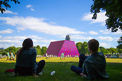 A couple gaze across the lawns of Hyde Park at artist Christo's 20m high installation on The Serpentine made from over 7000 barrels, titled The Mastaba, which will be on the Serpentine until 23 September 2018. The Installation is comprised of 7,506 horizontally stacked barrels. It is 20m high, 30m wide and 40m long. Hyde Park, London, June 18 2018.