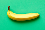 Close up of a ripe banana isolated on green background.