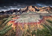 Stormlight after an early morning storm near sunrise brings out the colors of the yellow mounds region of the Badlands. The red and yellow colors are due to the later oxidation of iron-bearing materials in the original sedimentary deposits; in this case they were formed at the bottom of the Pierre Sea, which once covered this region. Badlands National Park, South Dakota, USA.