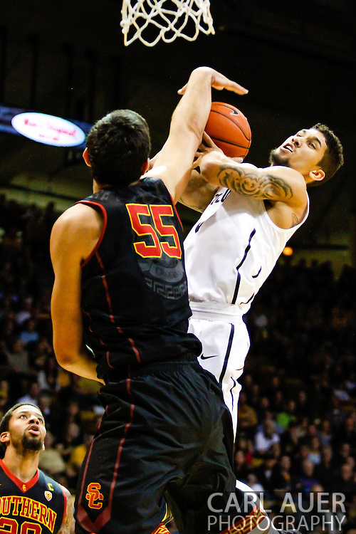 January 18th, 2014:  USC Trojans senior center Omar Oraby (55) attempts to stop a shot by Colorado Buffaloes junior guard Askia Booker (0) in the second half of the NCAA Basketball game between the USC Trojans and the University of Colorado Buffaloes at the Coors Events Center in Boulder, Colorado