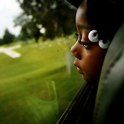 Destinee Mason (age 4), looks out a bus window at a re-creation of Mt. Olivet at Holy Land USA in Bedford, Virginia. Christians consider Mt. Olivet a hallowed place because it is the place where Jesus ascended to heaven, and the place where he is to return. Holy Land USA is a walking or motorized tour following key events in the life of Christ. Destinee was taking the tour with a church group who traveled 3 1/2 hours from Emporia, Virginia.<br /> Picture taken 6/13/2009