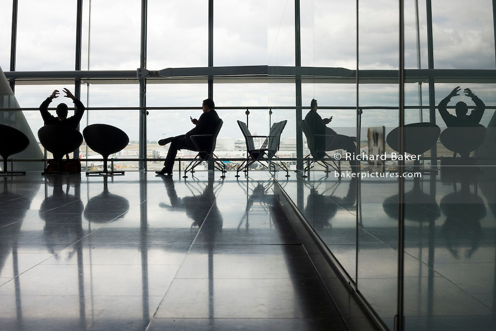 The silhouettes of departing passengers against the strong natural light from the vast windows of Heathrow Terminal 5