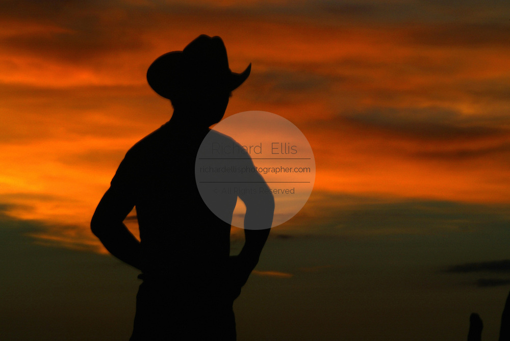 A cowboy watches the setting sun over Monument Valley on the southern border of Utah with northern Arizona. The valley lies within the range of the Navajo Nation Reservation. The Navajo name for the valley is Tsé Bii' Ndzisgaii - Valley of the Rocks.