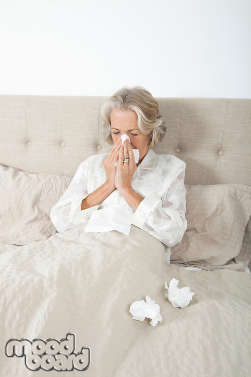 Unwell senior woman blowing nose in bed