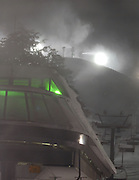 The upper section of Boyne Highlands Heather Express lift glows green while the resorts new Low Energy snow guns shoot out plumes of manmade snow on the slopes above.