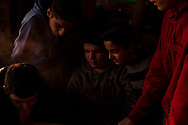 Boys gather at a dining room table, smoking and watching YouTube videos on a phone as the sun sets.<br />