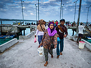 03 AUGUST 2017 - KUTA, BALI, INDONESIA: A woman and her husband walk along the Jimbrana Beach jetty after he came back to shore from a local trawler fishing off the coast of Bali. The beach is close to the airport and a short drive from other beaches in southeast Bali. Jimbrana was originally a fishing village with a busy local market. About 25 years ago, developers started building restaurants and hotels along the beach and land prices are rising. The new emphasis on tourism is changing the nature of the area but the fishermen are still busy very early in the morning.     PHOTO BY JACK KURTZ