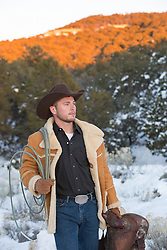 cowboy in a shearling coat with a lasso and saddle outdoors on a snowy mountain