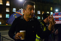 """A pro-Brexit campaigner argues with members of the public and pro-remain campaigners after they disembark from a bus emblazoned with """"Bollox to Brexit"""" as it arrives at Steve Bray's ongoing pro-remain protest at Old Palace Yard outside Parliament. Westminster, London, December 20 2018."""