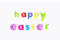 Colorful alphabet magnets spell 'happy Easter' over white background