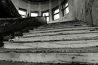"""""""Il destino d'Italia è sul mare"""" si legge al suo ingresso... Una lunga storia, quella di un'imponente opera circondata dal verde e nata, pare, dal primo colpo di piccone di Benito Mussolini nel 1934. Situata sul seno di ponente del porto, di fronte al Castello Svevo, è stata inaugurata nel 1937 come Accademia Marinara denominata """"Collegio Navale della Gioventù Italiana del Littorio"""". Durante la seconda guerra mondiale, con il trasferimento a Brindisi della famiglia reale fuggita da Roma, è diventata sede dell'Accademia Navale di Livorno dal 1943 al 1946. In seguito la competenza venne affidata al Comune di Brindisi ma la struttura fu destinata all'accoglienza e all'istruzione di profughi giuliani e dalmati prendendo il nome di """"Collegio Niccolò Tommaseo"""", dal letterato nato in Dalmazia nel 1802 e sostenitore della fratellanza tra slavi e italiani. Cominciava intanto il declino... Nel 1951 venne chiuso come Scuola convitto conservando la sede dell'Istituto Nautico e di altre scuole fino a quando, con il passaggio di proprietà alla Regione, nel 1977 è stato dichiarato inagibile. Nonostante gli accertati problemi di sicurezza, nel 1978 il Comune chiese alla Regione l'utilizzo di parte della struttura per la sistemazione temporanea di una decina di famiglie senza tetto. Dal rigore della cultura militare alla clemenza della povertà... il Collegio diventa un condominio, anzi un ghetto,  trasformato negli interni a piacimento dei nuovi abitanti, famiglie che negli anni sono diventate oltre duecento, sfrattate solo nel 1999 con l'assegnazione di nuovi appartamenti.  Il Tommaseo viene chiuso e murato in attesa di nuove destinazioni d'uso.... Nel dicembre 2010, a seguito di un accordo con la Regione e la Provincia, il Comune di Brindisi ne è tornato in possesso con l'impegno di presentare un progetto di recupero. Nel frattempo, nonostante muri e recinzioni, qualcuno aveva creato un varco.... oggi i ragazzi giocano alla guerra, in uno scenario ideale per allarmanti emulazioni."""