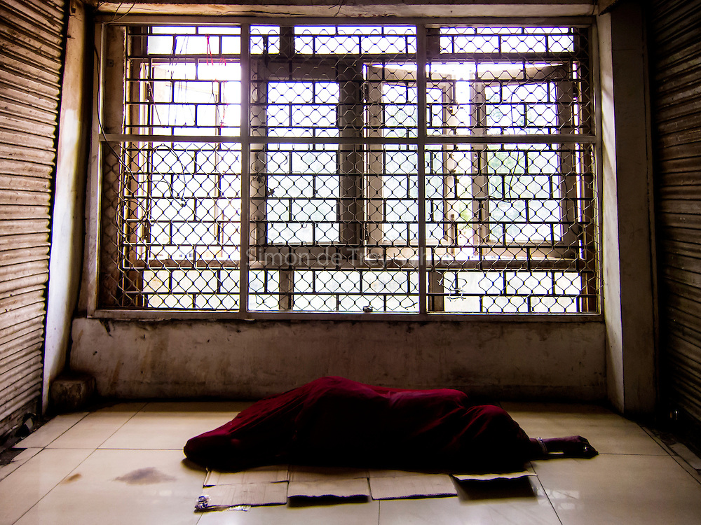 17th April 2016, New Delhi. A woman sleeps on the floor of a shopping complex in New Delhi, India on the 17th April 2016<br /> <br /> Sleeping in the outdoors is common in Asia due to a warmer climate and the fact that personal privacy for sleep is not so culturally ingrained as it is in the West. New Delhi (where most of these images were taken) is a harsh city both in climate and environment and for those working long hours, often in hard manual labour, sleep and rest is something fallen into when exhaustion overwhelms, no matter the place or circumstance. Then there are the homeless, in Delhi figures for them from Government and NGO sources vary wildly from 25,000 to more than 10 times that. Others public sleepers may simply be travellers having a siesta along the way.<br /> <br /> PHOTOGRAPH BY AND COPYRIGHT OF SIMON DE TREY-WHITE, photographer in Delhi<br /> <br /> + 91 98103 99809<br /> email: simon@simondetreywhite.com