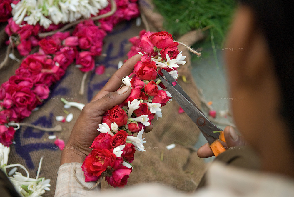 a man arranging flowers at the morning flower market on Baba Kharak Singh Marg near hanuman mandir in New Delhi
