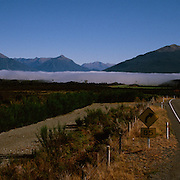 Early morning mist in a valley surrounded by mountain ranges on a deserted road in New Zealand. Photo Tim Clayton