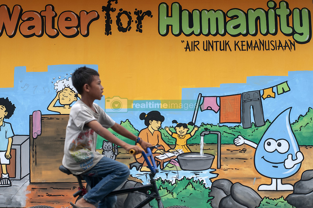 March 23, 2019 - Palu, Central Sulawesi, Indonesia - A child affected by a disaster passes in front of a water mural in the Duyu Temporary Shelter complex, Palu, Central Sulawesi, Indonesia, Saturday, March 23, 2019. Refugees in the shelter also commemorate Water World Day by making water-themed murals on the walls of shelters and providing water in containers for hand washing. (Credit Image: © Basri Marzuki/NurPhoto via ZUMA Press)