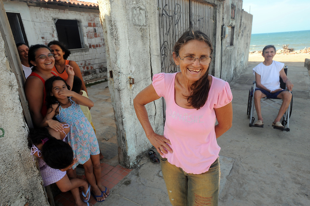 Maria Ines De Nascimento laughs outside her house with friends and her brother Jamie. The family have succeeded in retaining their house despite government efforts to knock it down. Fortaleza. Ceasa province, Brazil.
