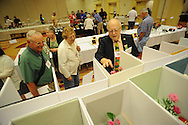 MOUNT LAUREL, NJ - JULY 26:  From left, Elton Smith, Ann Smith and judge Gary Barlow view miniature rose displays during the 2014 National Miniature Rose Show, hosted by the West Jersey Rose Society at the Hotel ML  July 26, 2014 in Mount Laurel, New Jersey. (Photo by William Thomas Cain/Cain Images)