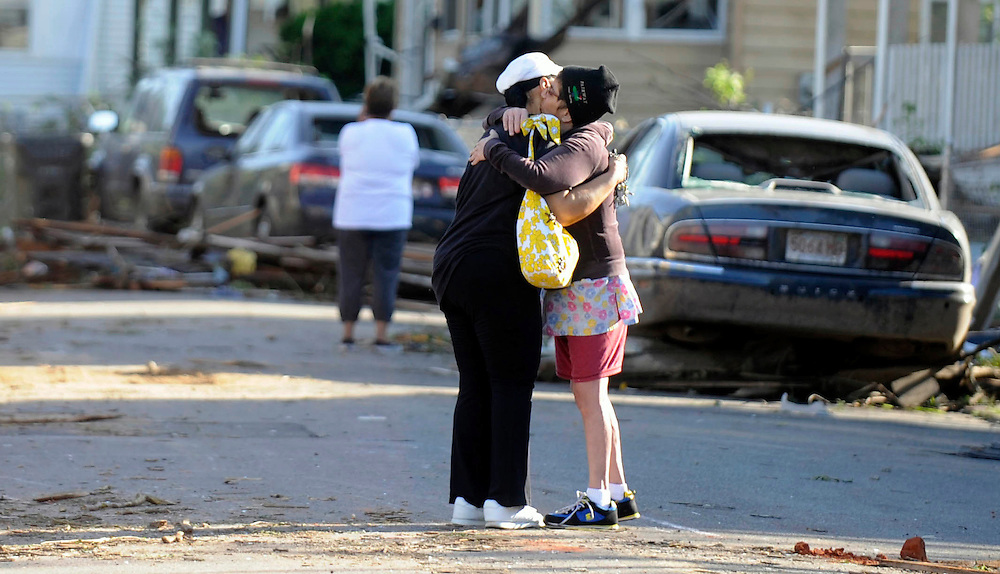 People embrace on a street damaged yesterday's tornado in Springfield, Mass., Thursday, June 2, 2011. Residents of 19 small communities in central and western Massachusetts were left to deal with widespread damage Thursday, one day after at least two late-afternoon tornadoes shocked emergency officials and residents more accustomed to dealing with snow and bone-chilling cold than funnel clouds spawned by spring storms. (AP Photo/Jessica Hill)