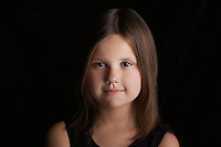 Girl (5-6) on black background portrait