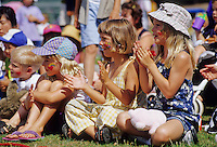 Kids 4-6, with their faces painted in colorful designs, clap for entertainer while watching an outdoor performance in Whistler, BC Canada.
