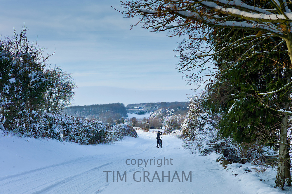 Cyclist in snowy lane stops to take photographs in The Cotswolds, UK