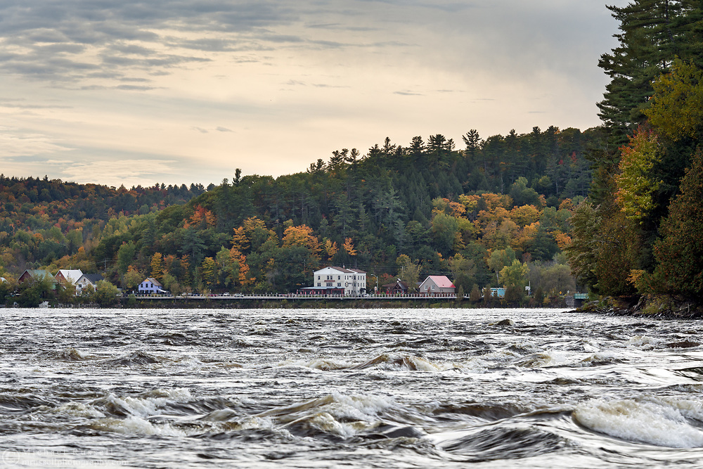 The Gatineau River and some riverfront buildings in Wakefield, Québec, Canada.  Photographed from next to the Wakefield Covered bridge over the Gatineau River.