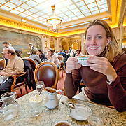 Young woman having coffee in Cafe Angelique in Paris