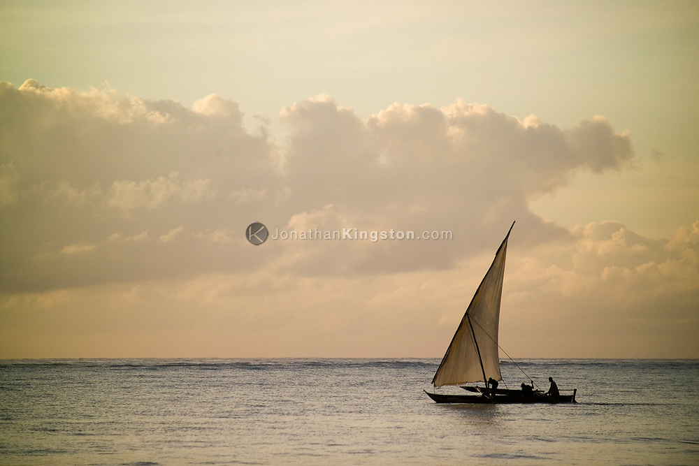 In early morning, a dhow, a carved-wooden boat, sails the Indian Ocean off the coast of Matemwe, Zanzibar, Tanzania.