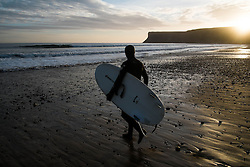 © Licensed to London News Pictures. <br /> 09/03/2015. <br /> <br /> Saltburn, United Kingdom<br /> <br /> Surfer Sam Davis walks out for an early morning surf as the sun rises over Huntcliff at Saltburn by the Sea.<br /> <br /> Photo credit : Ian Forsyth/LNP