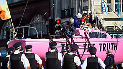 "© Licensed to London News Pictures. 19/04/2019. LONDON, UK. Police officers prepare to remove the last activist from the pink boat at Oxford Circus during ""London: International Rebellion"", on day five of a protest organised by Extinction Rebellion.  Protesters are demanding that governments take action against climate change.  Police have issued a section 14 order requiring protesters to convene at Marble Arch only so that the protest can continue.  Photo credit: Stephen Chung/LNP"