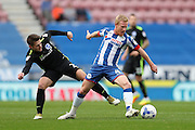 Wigan Athletic midfielder David Perkins (4) and Brighton & Hove Albion midfielder Oliver Norwood (21) during the EFL Sky Bet Championship match between Wigan Athletic and Brighton and Hove Albion at the DW Stadium, Wigan, England on 22 October 2016.