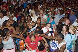 In a series of three photos people are seen in the audience reacting aggressively to a what seems tourist family (man and boy in red shirt, woman and girl wearing Wawa Welcome America caps).
