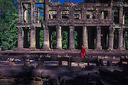 A monk visits the ruins of Ta Phrom.