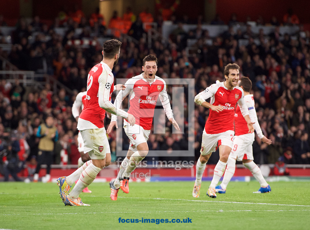 Mesut Ozil of Arsenal (middle) celebrates after heading the ball past goalkeeper Eduardo of Dinamo Zagreb to score the opening goal during the UEFA Champions League match at the Emirates Stadium, London<br /> Picture by Alan Stanford/Focus Images Ltd +44 7915 056117<br /> 24/11/2015
