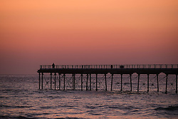 © Licensed to London News Pictures. <br /> 09/05/2016. <br /> Saltburn by the Sea, UK.  <br /> <br /> A man stands on the end of the pier at first light at Saltburn by the Sea in North Yorkshire. After the warmest day of the year yesterday temperatures are due to drop slowly over the rest of the week.<br /> <br /> Photo credit: Ian Forsyth/LNP