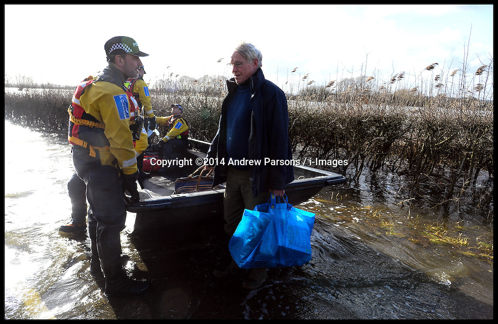 A member of the public waits for lift by the by the rescue boat on the Somerset Levels to get back to his house cut off by the floods. The Somerset Levels are Flooded due to heavy rain in January. London, United Kingdom. Tuesday, 4th February 2014. Picture by Andrew Parsons / i-Images