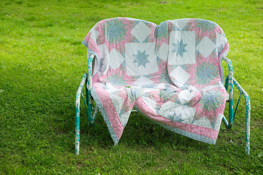 Country quilt on a lawn rocker in a yard