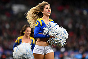 A smiling LA Rams cheerleader runs on the pitch during the International Series match between Los Angeles Rams and Cincinnati Bengals at Wembley Stadium, London, England on 27 October 2019.