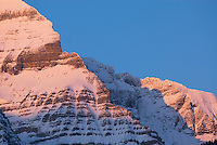 Sheer snow covered cliffs of Mount Robson 3,954 m (12,972 ft) glowing in the winter sunset, Mount Robson Provincial Park British Columbia Canada