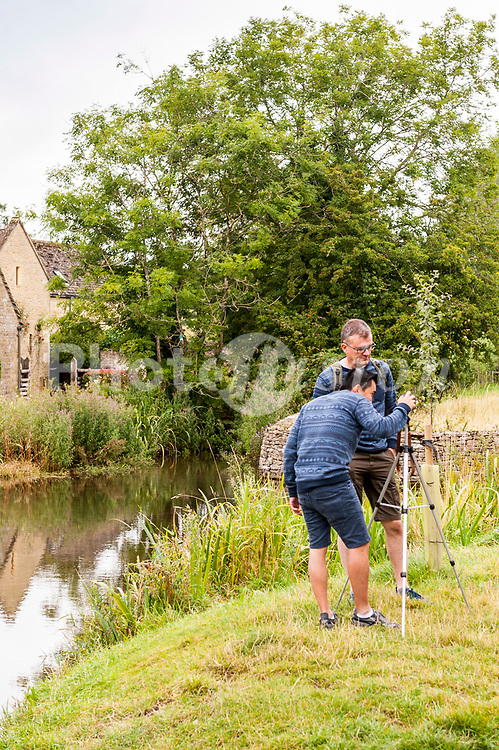 Tourists taking photos in Lower Slaughter , Gloucestershire , England , Britain , Uk