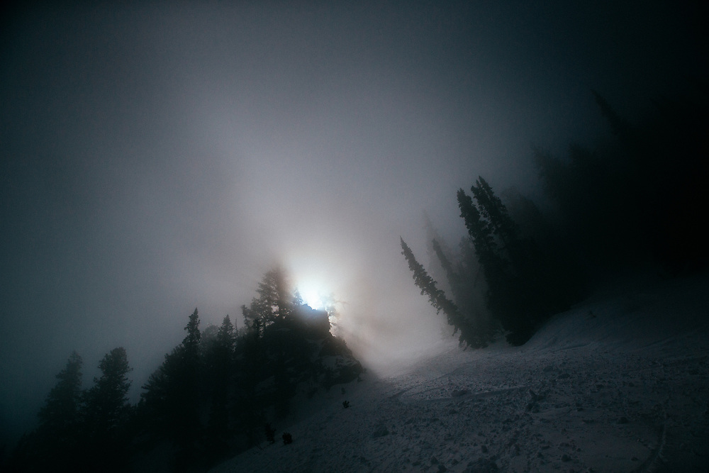 Jay Goodrich's ski tracks are illuminated by the sun breaking out of fog in the early morning hours in the Teton backcountry.