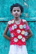 Portrait of girl in red crochet top against green wall,  Mawlamyine