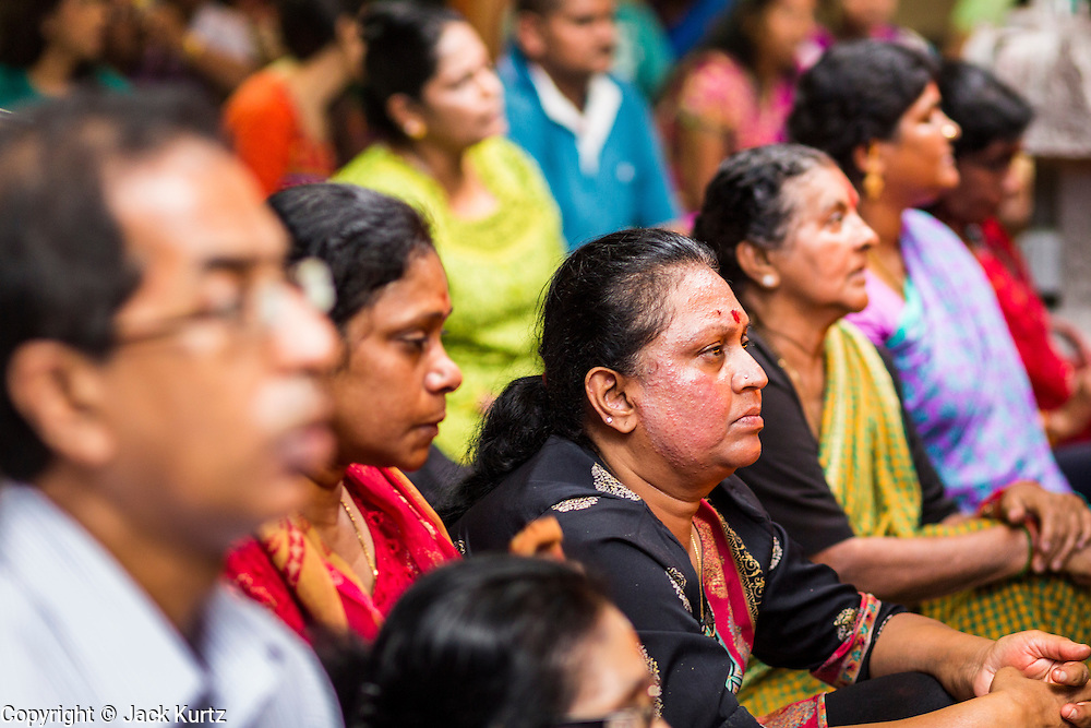 07 JANUARY 2014 - SINGAPORE:   People pray during afternoon pooja in Sri Veeramakaliamman Temple, a Hindu temple located in Little India in the southern part of Singapore. The Sri Veeramakaliamman Temple is dedicated to the Hindu goddess Kali, fierce embodiment of Shakti and the god Shiva's wife, Parvati. Kali has always been popular in Bengal, the birthplace of the labourers who built this temple in 1881. Images of Kali within the temple show her wearing a garland of skulls and ripping out the insides of her victims, and Kali sharing more peaceful family moments with her sons Ganesha and Murugan. The building is constructed in the style of South Indian Tamil temples common in Tamil Nadu as opposed to the style of Northeastern Indian Kali temples in Bengal. PHOTO BY JACK KURTZ