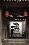 """A woman walks through a traditional doorway in Chuandixia, decorated with the character """"fu"""" meaning """"happiness."""" In 1995, a combination of opportunity and initiative by villagers changed the fate of Chuandixia. As tourism flourished, word circulated in Beijing about the village and its pristine Ming architecture. Though village walls were branded with red slogans from the 1950's and 1960's, the buildings themselves remained unscathed, unlike many other historical relics in China. ...."""