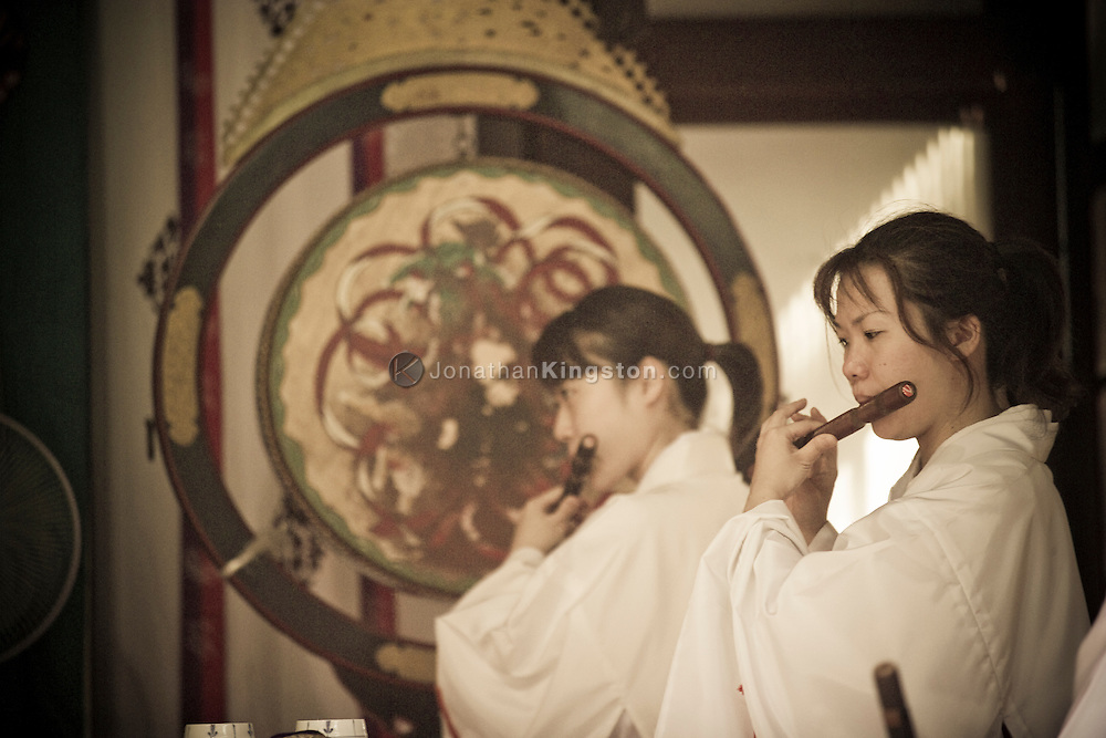Two women playing the Shinobue flute in the Ikukunitama Shrine, a Shinto Shrine, in Osaka, Japan.