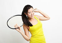 Portrait of young Asian woman holding tennis racket over her shoulder against white background