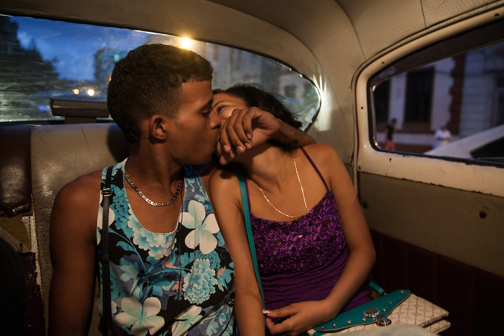 A young couple kiss inside a taxi as the night falls over the city in Havana, Cuba.<br />